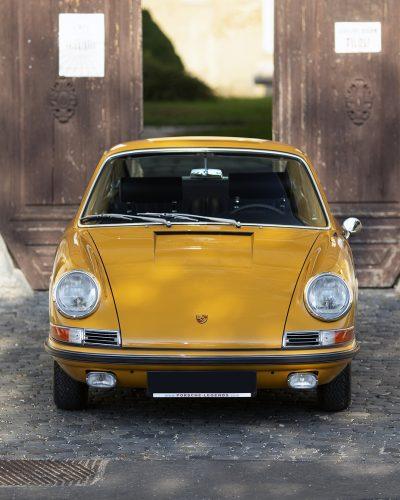 Gelber Porsche 911S vor Holztor