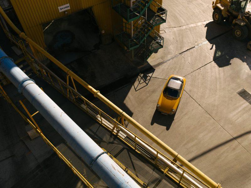 Gelber Porsche auf Fabriksgelände