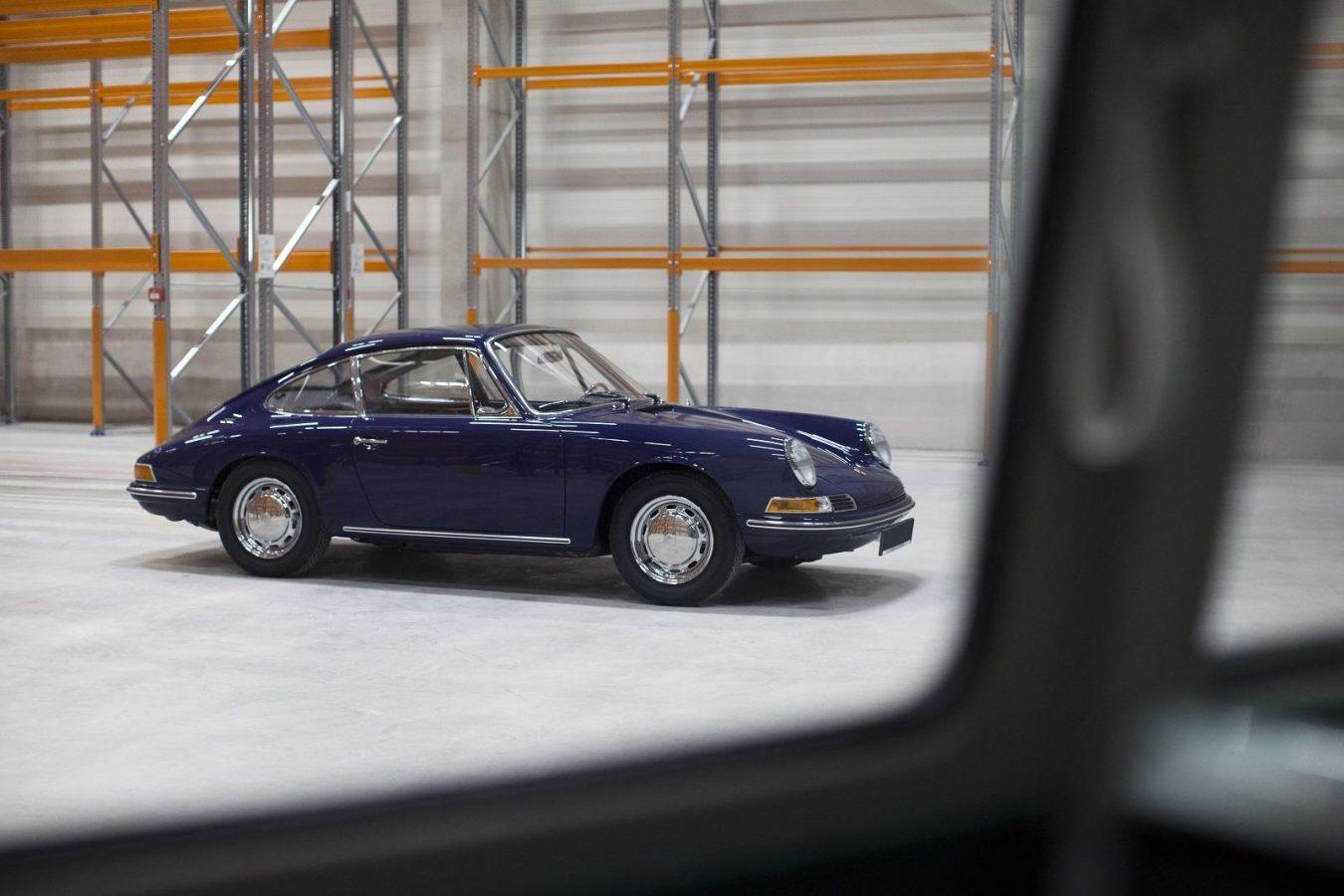 Blauer von der Seite Porsche 911 SWB vor Lagerregalen