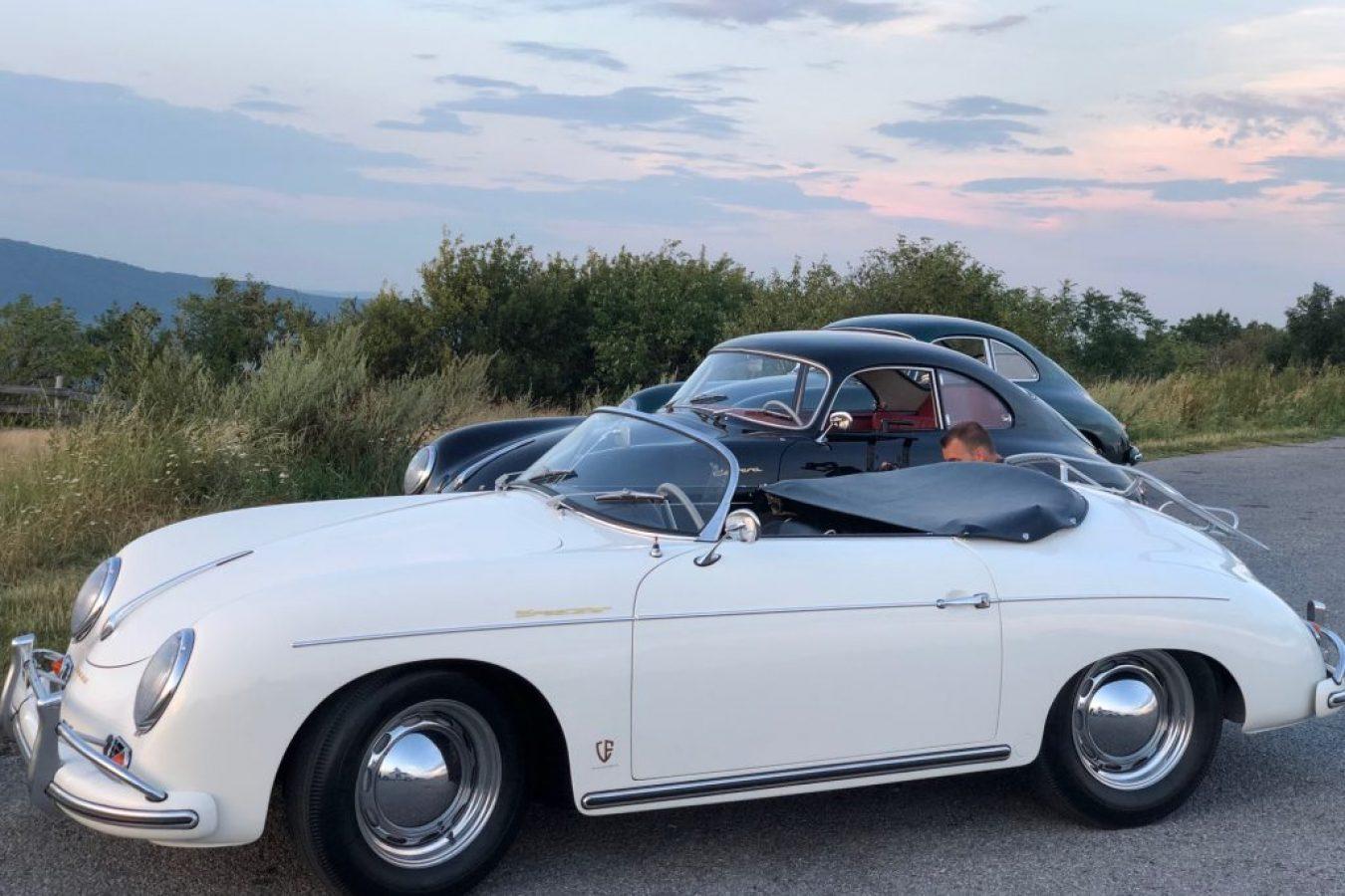 Ein weißer Porsche und zwei schwarze Porsche von der Seite