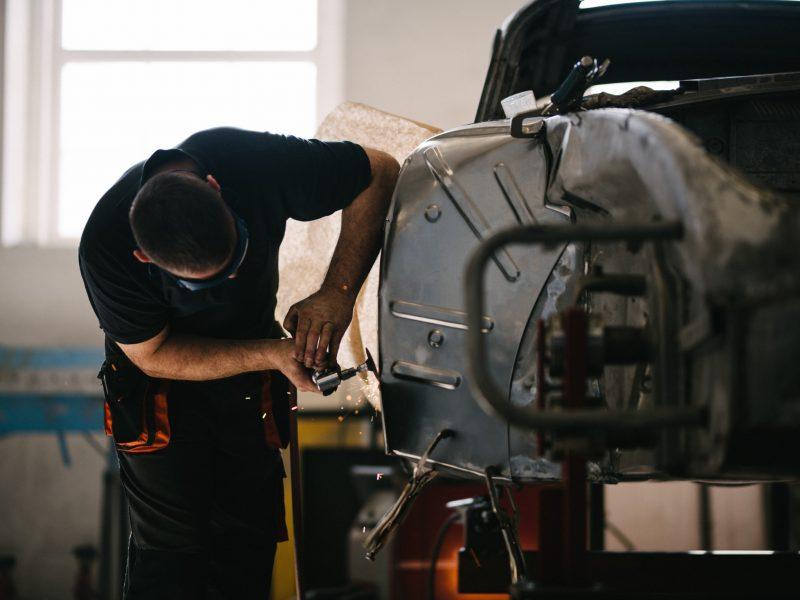 Arbeiter arbeitet an Karosserie in Werkstatt