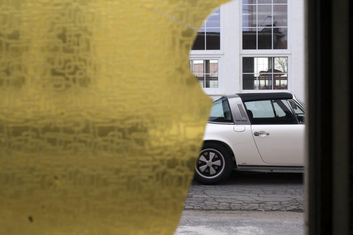Cremeweißer Porsche 911E Targa aus dem Fenster